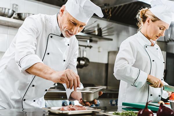 focused-male-and-female-chefs-in-uniform-preparing-FSFCDTLneighborhood